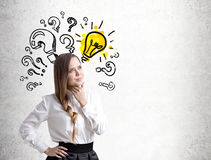 Pensive young woman, question marks and bulb Stock Photos