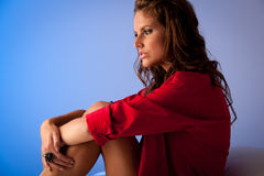 Pensive young woman in red shirt sitting in bed on white silk sh Stock Images