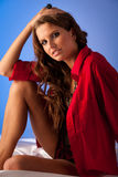 Pensive young woman in red shirt sitting in bed on white silk sh Royalty Free Stock Images