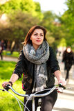 Pensive young woman riding bicycle in green city park. Pensive young woman riding a bicycle in the green city park Stock Image