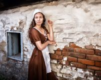 Pensive young woman in a rustic dress standing near old brick wall in old house feel lonely. Cinderella style. Sad woman in a rustic dress standing near old Royalty Free Stock Photography