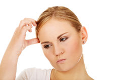Pensive young woman scratching her head Royalty Free Stock Photos