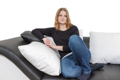 Pensive young woman is sitting on a black and white couch Stock Photo