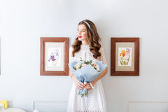 Pensive young woman standing and holding bouquet of flowers Royalty Free Stock Photo