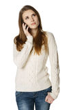Pensive young woman talking on cell phone. Looking up, over white background stock images