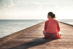Pensive young woman tourist enjoy her life sitting on pier beach with infinity view copy space. Pensive young woman tourist enjoy her life sitting on pier beach royalty free stock image