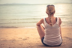 Pensive young woman tourist sitting on beach and looking into the distance stock photo