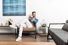 Pensive youthful guy relaxing at home atmosphere Stock Image