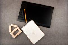Pentablet, блокнот, карандаш и игрушка расквартировывают положение на серой предпосылке Стоковые Изображения RF