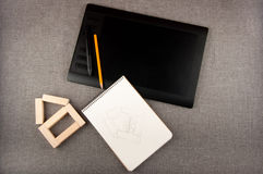 Pentablet, notepad, pencil and toy house lay on grey background Royalty Free Stock Images