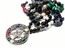 Pentacle. The pentacle pendant on this necklace is Wiccan. The five stones represent the four elements plus spirit - red for fire, blue for water, green for Royalty Free Stock Image