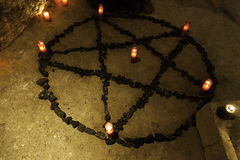 Satanic pentacle with candles in a dark ritual. Pentacle satanic with candles in a dark ritual, detail of black magic and beliefs Stock Image