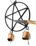Pentacle Wind Chime and Athame. Athame knife points to the back wrought iron pentacle star wind chime with rustic bells,  on white Stock Photo