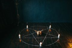 Pentagram circle with candles on wooden floor. Pentagram circle with candles on black wooden floor. Dark magic ritual with occult and esoteric symbols Royalty Free Stock Photo