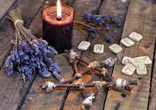 Pentagram with lavender flowers, old runes and black candle on planks. Occult, esoteric, divination and wicca concept. Mystic and vintage background with old royalty free stock images