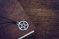 Pentagram pendant and book Stock Photo