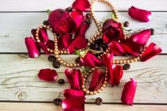 Pentals de rosas vermelhas e de uma colar Imagens de Stock
