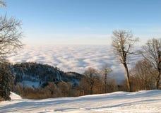 Pente blanche de ski au-dessus des nuages gonflés Photo stock