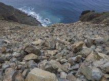 Pente raide des pierres en baisse de roche avec les falaises de lave et la mer bleue Images stock