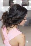 Penteado elegante bonito na menina bonita do cabelo escuro com um ornamento das pedras em seu cabelo, penteado da noite para o we Fotografia de Stock