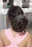 Penteado elegante bonito na menina bonita do cabelo escuro com um ornamento das pedras em seu cabelo, penteado da noite para o we Imagens de Stock Royalty Free