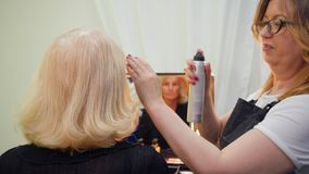 Penteado para a mulher superior no salão de beleza do cabeleireiro vídeos de arquivo