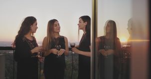 On the penthouse balcony at the home party ladies drinking wine and spending a great time together. 4k stock footage
