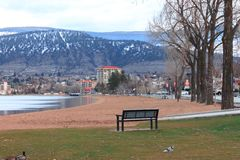 Penticton coast. An empty bench by a sandy beach on the coast of Penticton, Okanagan Valley, and the town and mountains in the background Stock Image