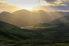 Pentland Hills mountain landscape near Edinburgh, with sunrays reflecting in a lake Royalty Free Stock Photos