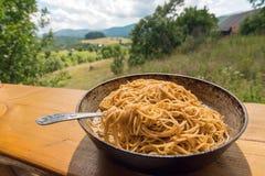 Pentola con gli spaghetti e forcella sul terrazzo della casa rurale, come simbolo della vita e dell'ambiente del villaggio Immagini Stock