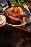 Pentola con la cena della cipolla e della costola principale con birra ed insalata Immagini Stock