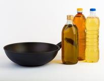 Pentola con le bottiglie di olio isolate su bianco Fotografia Stock