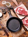 Pentola del ghisa con la bistecca cruda del ribeye su fondo di legno Immagini Stock Libere da Diritti
