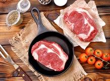 Pentola del ghisa con la bistecca cruda del ribeye su fondo di legno Fotografie Stock