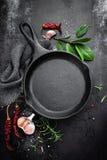 Pentola e spezie del ghisa sul fondo culinario del metallo nero fotografia stock
