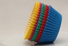 Pentole di carta colorate che cuociono le tazze per i bigné ed i muffin Immagini Stock Libere da Diritti