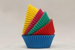 Pentole di carta colorate che cuociono le tazze per i bigné ed i muffin Fotografia Stock