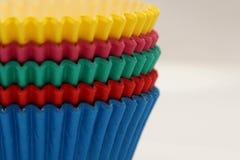 Pentole di carta colorate che cuociono le tazze per i bigné ed i muffin Fotografia Stock Libera da Diritti