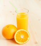 Pełny szkło sok pomarańczowy z słomianą pobliską owocową pomarańcze Fotografia Stock