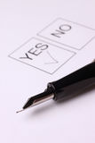 Penyes. The close-up of a pen and white checklist with a checkboxes with words YES and NO Stock Photography