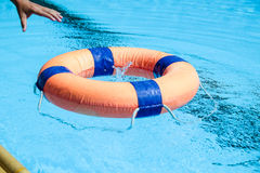 Peolple throw Life ring floating to someone. In the pool Stock Photo