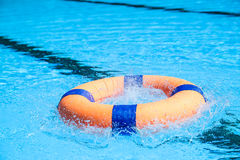 Peolple throw Life ring floating to someone. In the pool Royalty Free Stock Photos