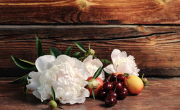Peonía, cereza y melocotón Todavía vida con las bayas y las flores frescas Imagenes de archivo