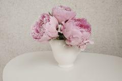 Peonías de Rose en una tabla blanca Fotografía de archivo