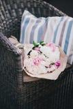 Peonías en una bolsa de papel que miente en una silla de mimbre fotos de archivo libres de regalías