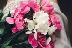 Peonías rosadas hermosas en las piernas de la muchacha del boho en el vestido bohemio blanco, visión superior Espacio para el tex fotos de archivo