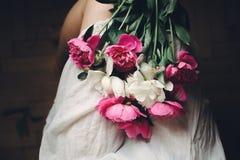 Peonías rosadas hermosas en las piernas de la muchacha del boho en el vestido bohemio blanco, visión superior Espacio para el tex foto de archivo libre de regalías