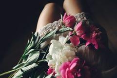 Peonías rosadas preciosas en las piernas de la muchacha del boho en el vestido bohemio blanco fotografía de archivo