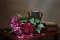 Peonías y un pote del café del vintage Imágenes de archivo libres de regalías