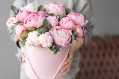 Peon?as rosadas en las manos de la mujer Flor hermosa de la peon?a para el cat?logo o la tienda en l?nea Concepto floral de la ti imagenes de archivo